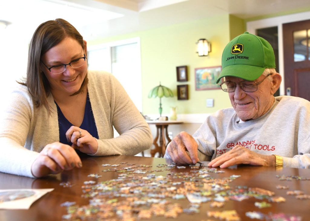 bethany life long term care resident completing a puzzle with nurse